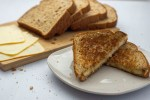Classic Grilled Cheese Sandwich wedges on a round white plate with sliced bread and cheese behind all on a white surface