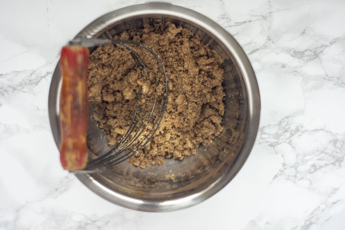 Stainless steel with a pastry blender combining cinnamon mixture with softened butter
