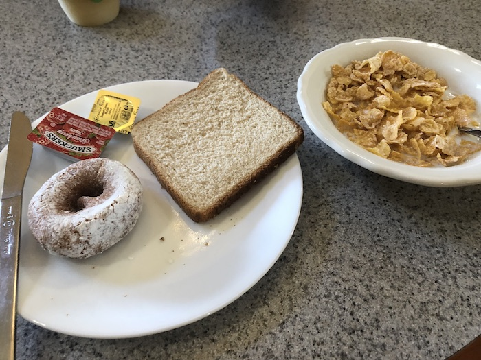 My Vacation in Food: Part 3: Round white plate with toast and a doughnut next to a bowl of cereal