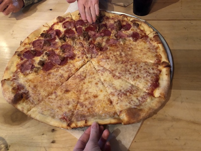 My Vacation in Food: Part 3: Two women's hands grabbing slices of a large pizza