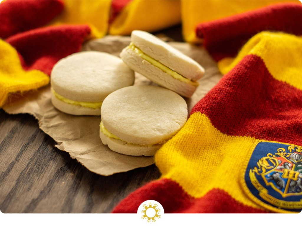 3 Canary Creams on a piece of brown butcher paper surrounded by a Gryffindor scarf on a wooden surface (with logo overlay)