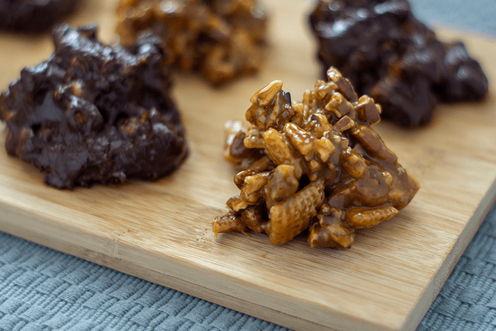 Caramel cockroach clusters with and without chocolate on a wooden serving dish placed on a grey-blue placemat on a wooden table