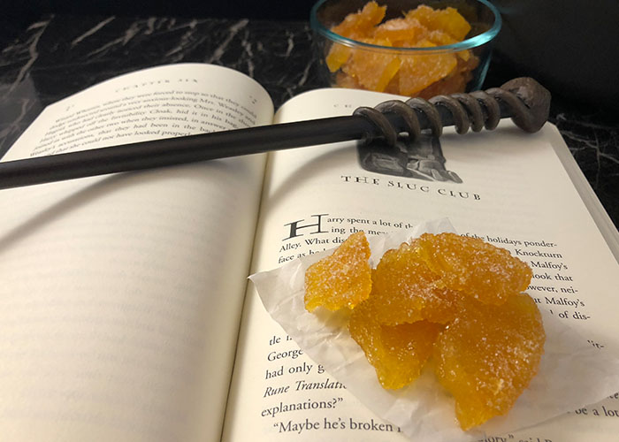 Crystallized Pineapple on a piece of wax paper sitting on an open Harry Potter book with a wand on top with a glass bowl of crystallized pineapple behind the book all on a black and white marble surface