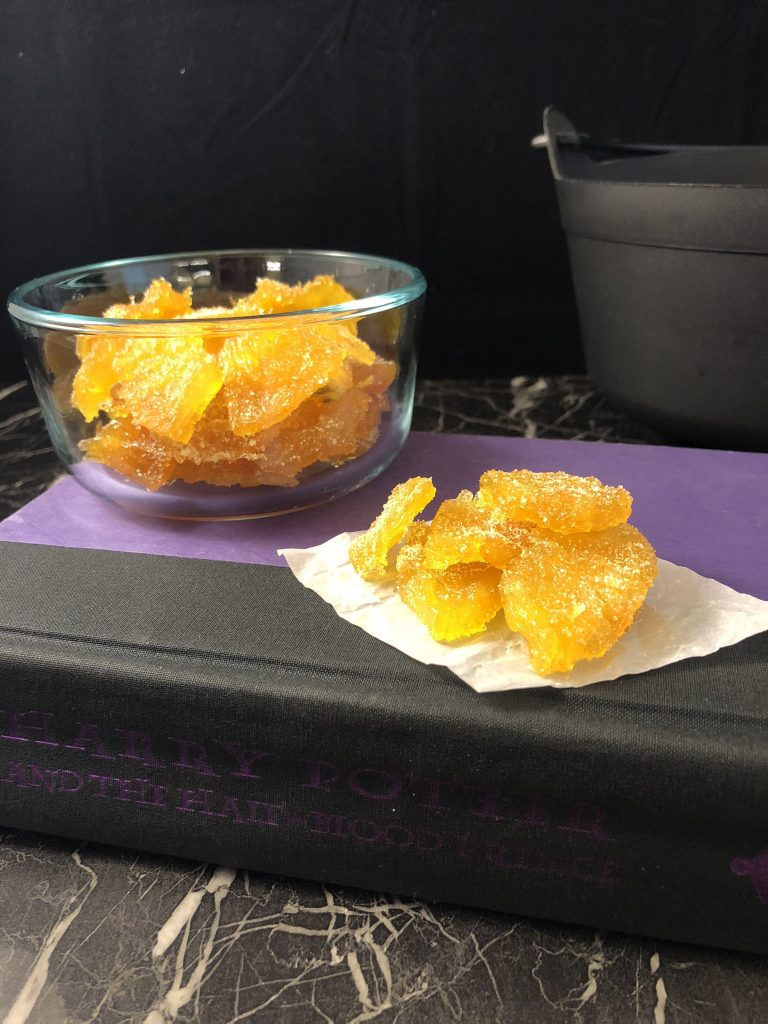 Crystallized pineapple on top of a piece of parchment paper with a glass bowl of more crystallized pineapple behind all sitting on a closed Harry Potter book on a black and white marble surface