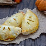 3 pumpkin pasties piled together on a brown paper with fall decorations behind all on a wooden surface (vertical with title overlay)