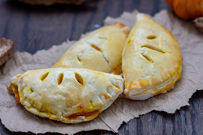 3 pumpkin pasties piled together on a brown paper with fall decorations behind all on a wooden surface