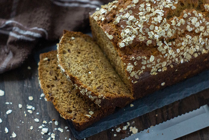 Banana Bread covered with oats on a slate serving plate next to a brown towel and a bread knife on a wooden surface