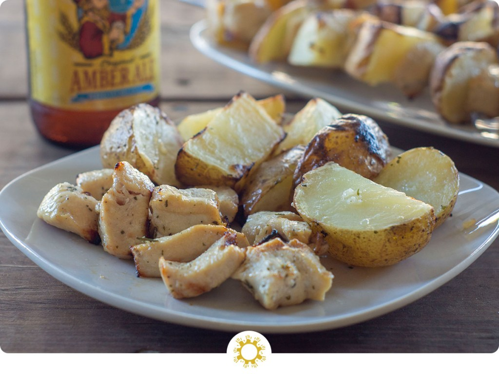 Plate with cooked chicken and potatoes with skewers in background and bottle of beer with logo overlay