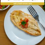 Grilled chicken topped with chopped tomatoes and cilantro next to a fork on a round white plate with a bunch of cilantro to the top right and a bowl of tomato salsa to the top left with a spoon all on a wooden surface (vertical with large title overlay)