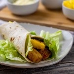 Hawaiian chicken wraps filled with bbq chicken, pineapple chunks, and lettuce in a flour tortilla over a bed of lettuce on a square white plate with a bamboo platter behind with round white bowls of cheese, lettuce, and pineapple all on a wooden surface