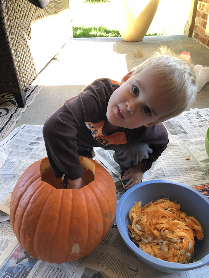Young boy cleaning out a pumpkin on the ground covered with newspaper
