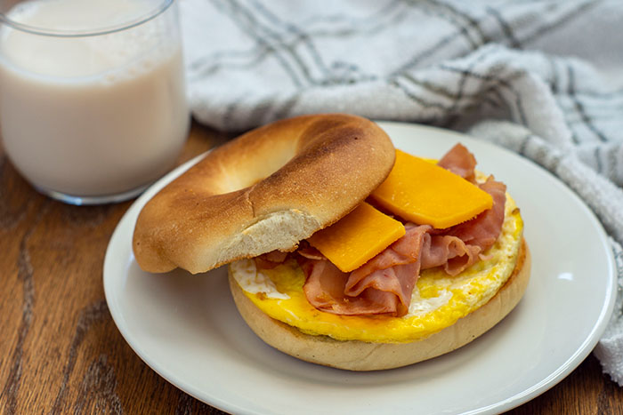 Breakfast bagel with egg, ham, and sliced cheese on a round white plate next to a glass of milk and a grey and white towel on a wooden surface
