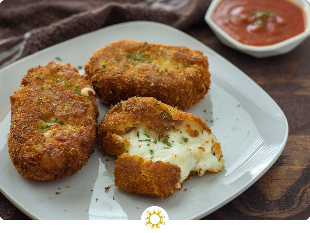 Fried mozzarella cakes with one broken open to show the cheese on a white plate next to a white bowl of marinara sauce with a brown towel in the background all on a dark wooden surface (with logo overlay)