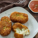 Fried mozzarella cakes with one broken open to show the cheese on a white plate next to a white bowl of marinara sauce with a brown towel in the background all on a dark wooden surface (vertical with title overlay)