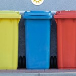 4 colorful garbage cans in a line on a sidewalk next to a building on a cobbled street (with title overlay)