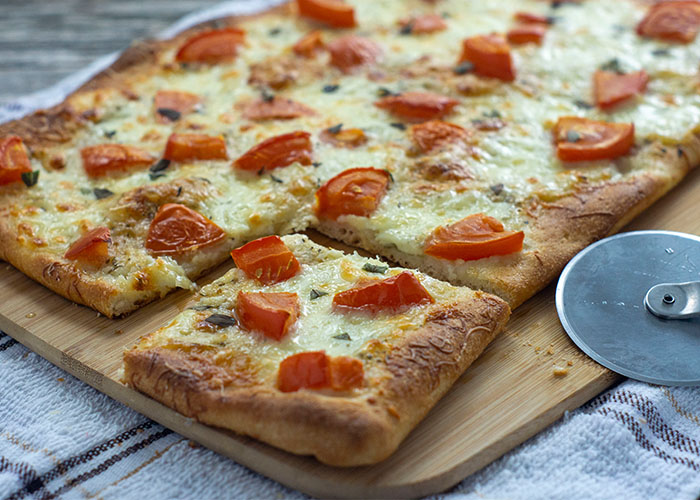 Mozzarella-Topped Flatbread on a bamboo cutting board with one square corner piece cut out next to a metal pizza cutter on a white and brown towel