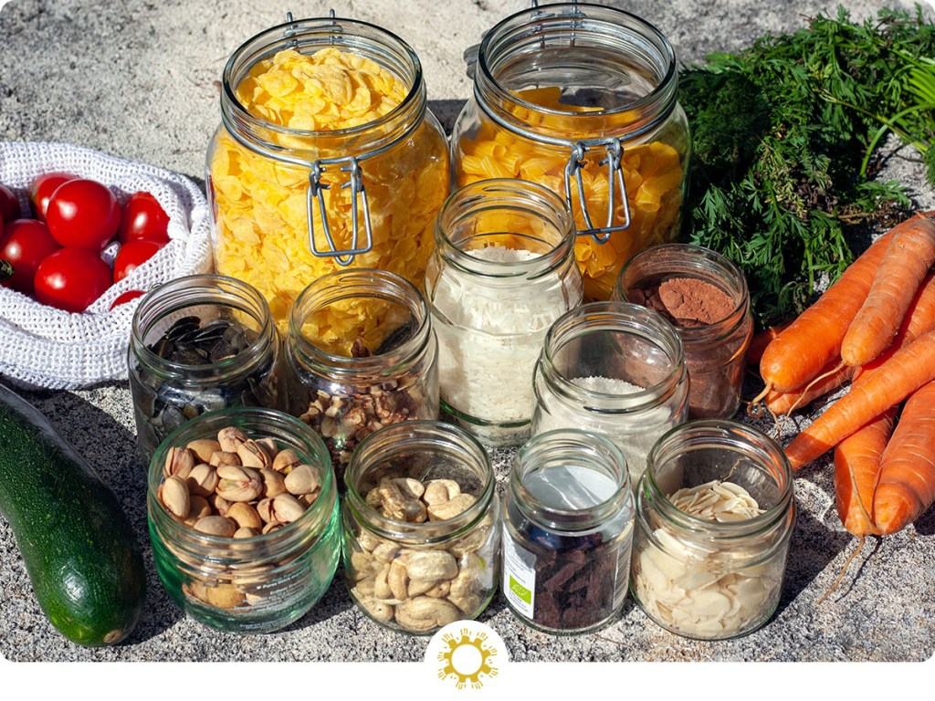 Assorted jars of dried foods next to loose carrots and tomatoes in a mesh bag all on a concrete surface (with logo overlay)