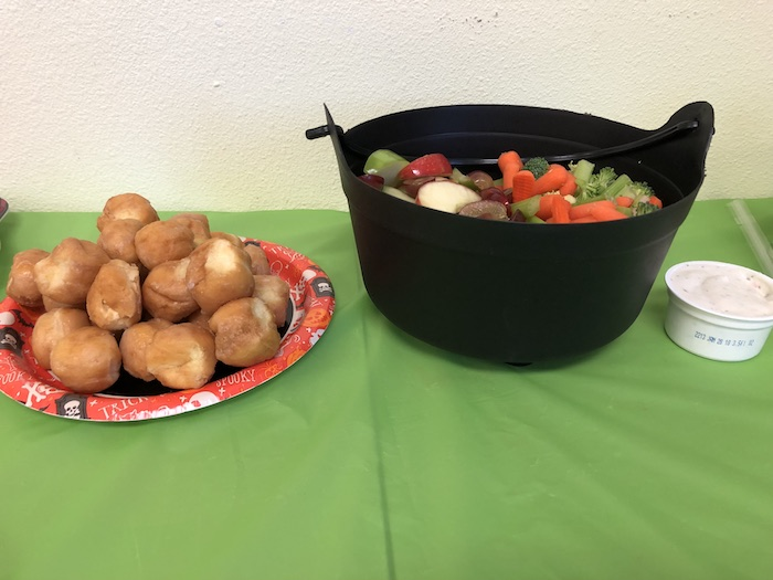 Sliced fruits and veggies in a black cauldron bucket next to a plate of doughnut holes
