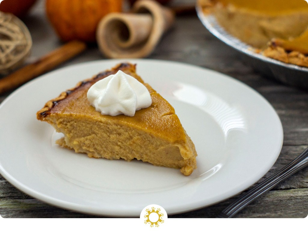 Slice of pumpkin pie topped with whipped cream on a round wooden plate in front of fall decorations on a wooden surface (with logo overlay)