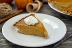Slice of pumpkin pie topped with whipped cream on a round wooden plate in front of fall decorations on a wooden surface