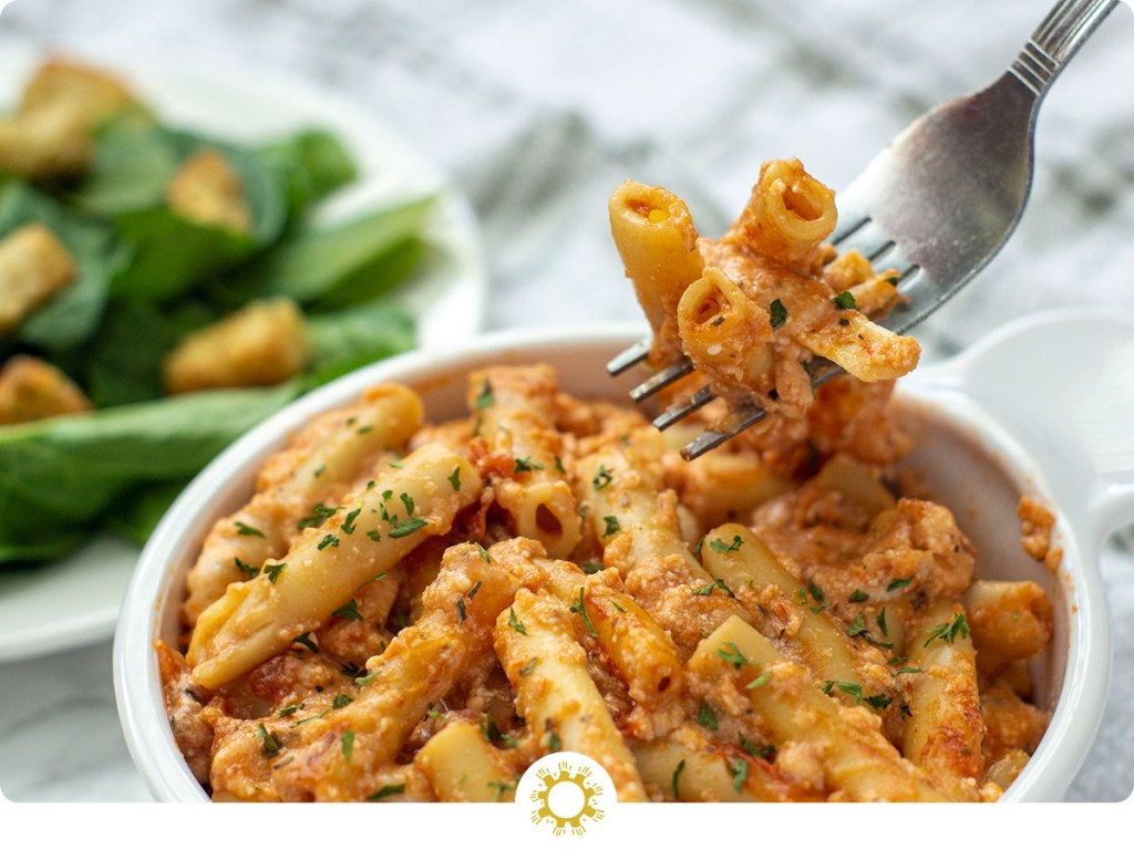 A bite of Baked Ziti in a white bowl being lifted by a fork (with logo overlay)