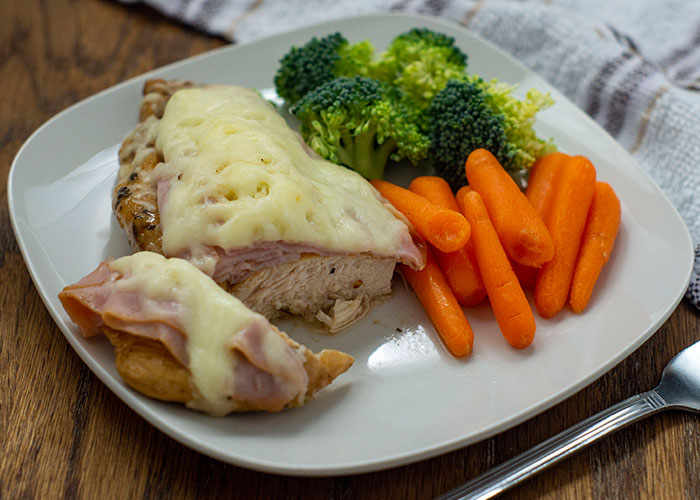 Cut piece of chicken cordon bleu with fresh carrots and broccoli on a square white plate with a stainless steel fork in front and a white and brown towel behind all on a wooden surface