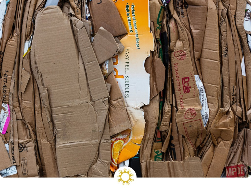 Pile of flattened cardboard boxes for recycling (with logo overlay)