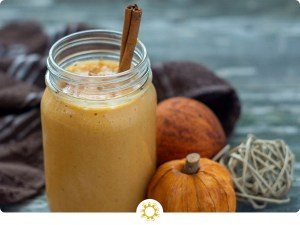 Pumpkin pie smoothie in a large mason jar with a stick of cinnamon sticking out next to fall decorations and a brown towel on a wooden surface (with logo overlay)