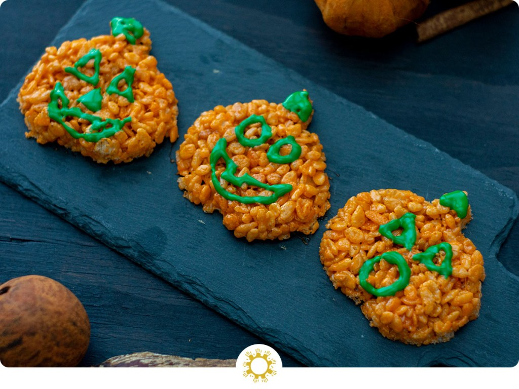 Pumpkin-shaped rice krispies with faces in green icing on a slate serving board on a dark wooden surface with fall decorations (with logo overlay)