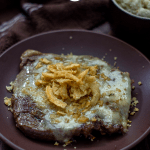 French Onion steak on a round brown plate with a brown towel and bowl of mashed potatoes behind all on a wooden surface (vertical with title overlay)