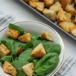 Italian-Style croutons on top of spinach leaves in a white bowl on top of a white and brown towel next to a metal baking sheet (vertical with title overlay)
