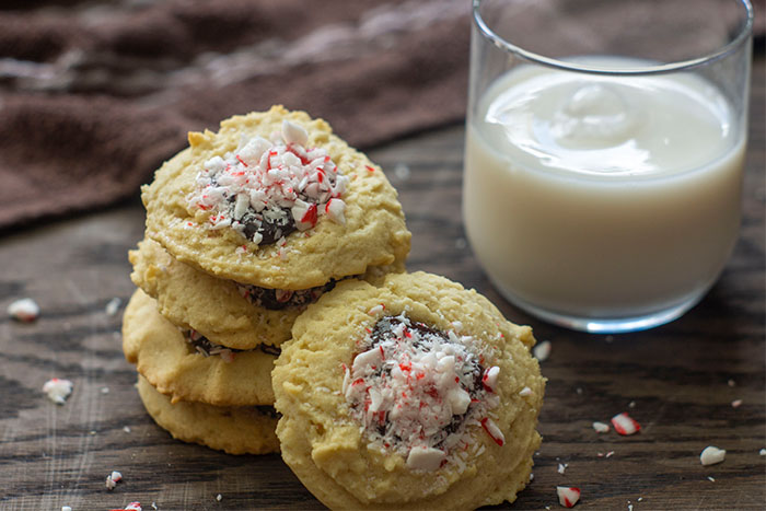 Stack of peppermint chocolate ganache thumbprint cookies surrounded by crushed peppermint and a glass of milk and brown towel behind all on a wooden surface