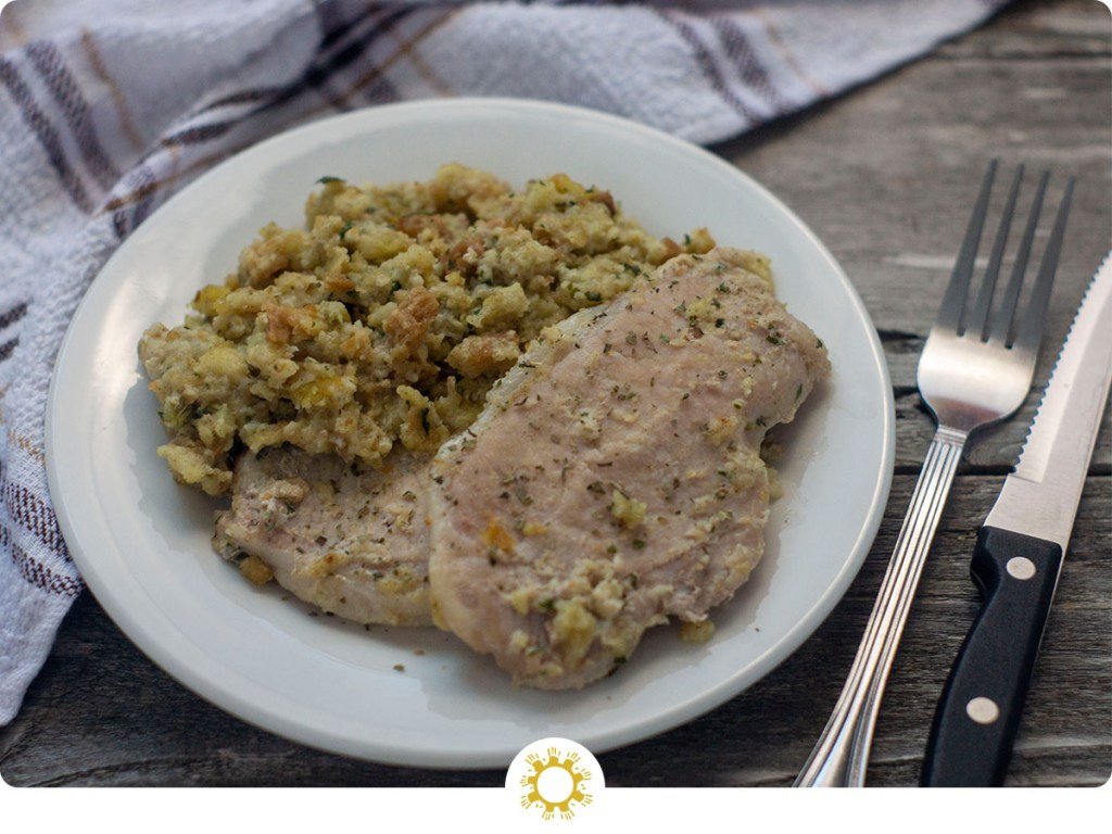 Un-stuffed Pork Chops on a round white plate with a white and grey towel behind and a fork in front on a wooden surface (with logo overlay)