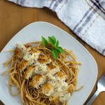 White Cheddar Chicken Pasta garnished with a sprig of basil on a square white plate next to a stainless steel fork with a white and brown towel behind all on a wooden surface (vertical with title overlay)