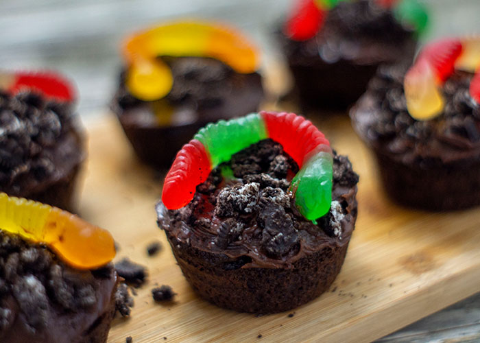 Dirt cupcakes covered with crushed oreos and topped with a gummy worm on a bamboo platter on a wooden surface
