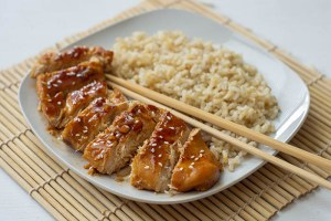 Orange chicken on a white plate with brown rice and chopsticks