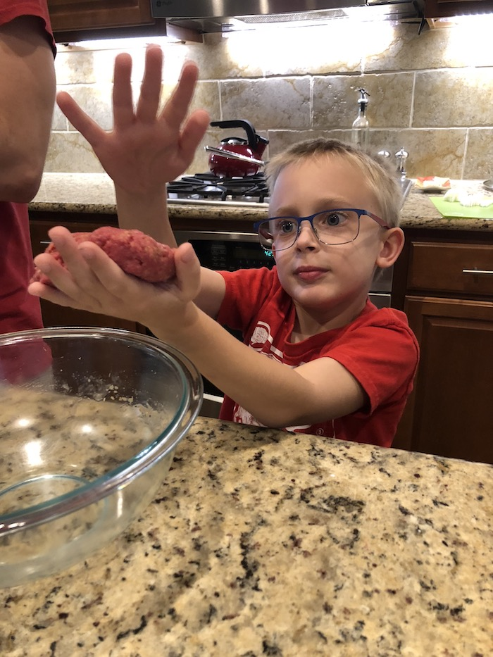 Young boy shaping ground beef into patties standing at a granite countertop