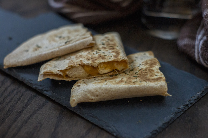 3 pieces of chicken and cheese quesadillas on a slate tray with a brown and white towel behind all on a wooden surface