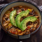 Chicken tortilla soup topped with sliced avocado and parsley in a brown bowl with a brown towel behind on a wooden surface (vertical with title overlay)