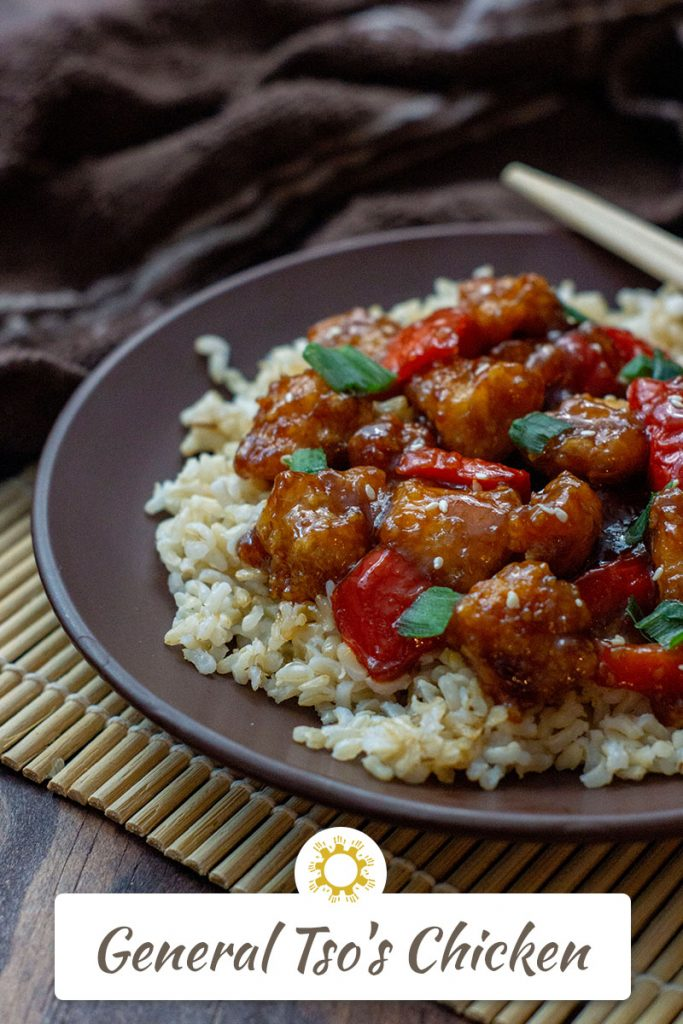 Quick & Easy General Tso's Chicken on a bed of rice on a round brown plate with bamboo chop sticks on top of a bamboo mat with a brown towel behind all on a wooden surface (vertical with title overlay)