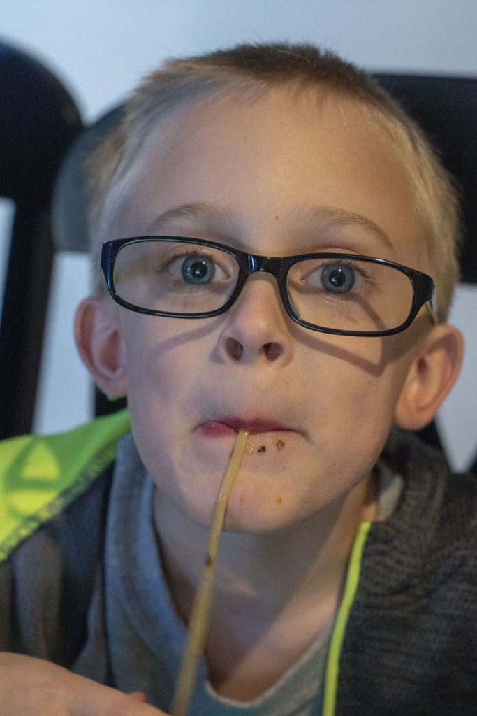 Young boy slurping noodles