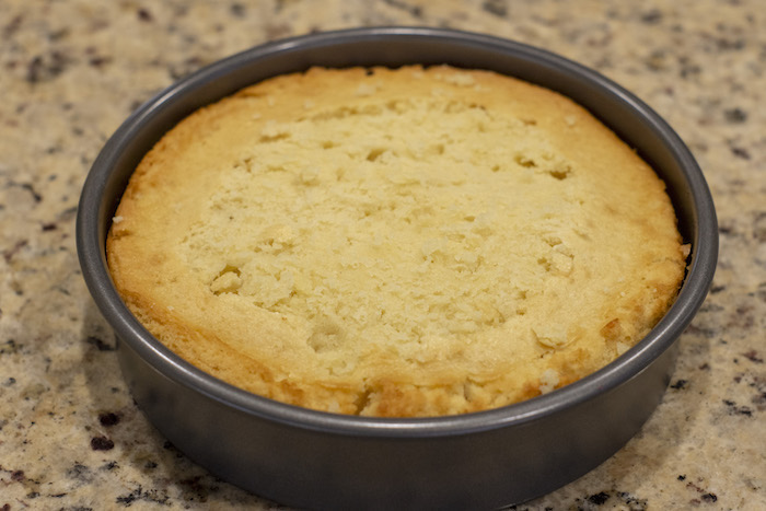 Baked cake with the top cut to level in a round metal cake pan on a granite surface