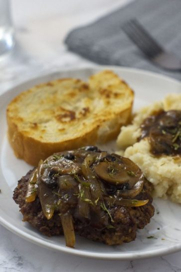 Salisbury Steak with mashed potatoes covered with salisbury gravy and a piece of garlic toast on a round white plate with a grey napkin and fork behind all on a white and grey marble surface (vertical)