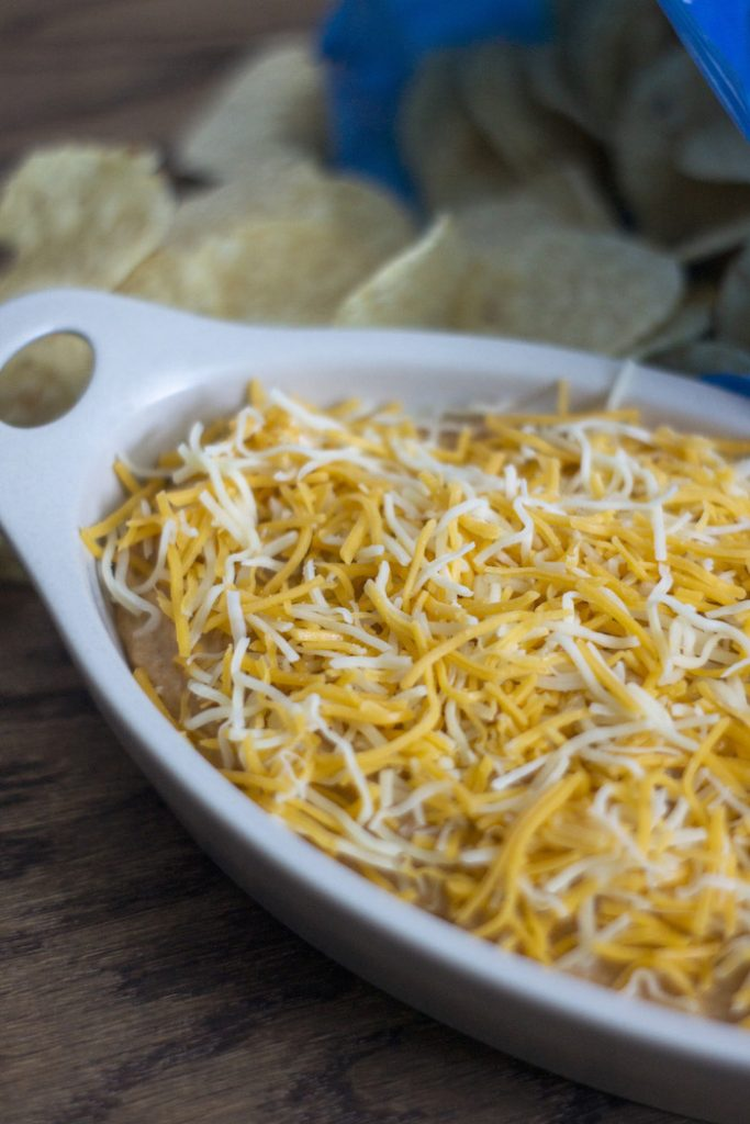 Taco Dip covered with shredded blended cheese in an off-white serving dish with round tortilla chips spilling out of the bag behind the dish all on a wooden surface (vertical)