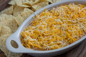 Taco Dip covered with shredded blended cheese in an off-white serving dish with round tortilla chips behind the dish all on a wooden surface