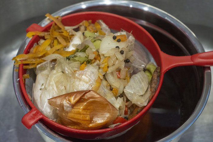 Vegetable scraps in a mesh strainer over a stainless steel bowl in a stainless steel sink