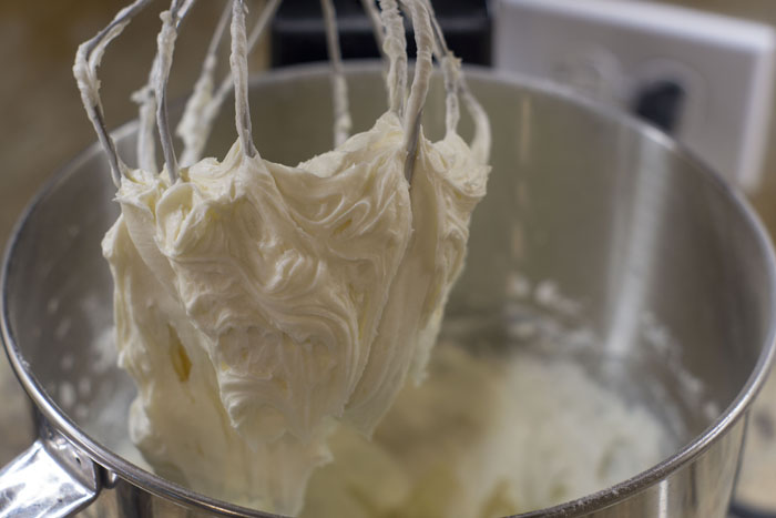 Cream cheese frosting on the wire whisk of a stand mixer