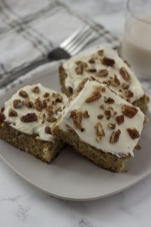 Three Banana Bread Bars topped with pecans on a square white plate with a stainless steel fork, glass of milk, and a white and grey towel behind the plate all on a white and grey marble surface (vertical)