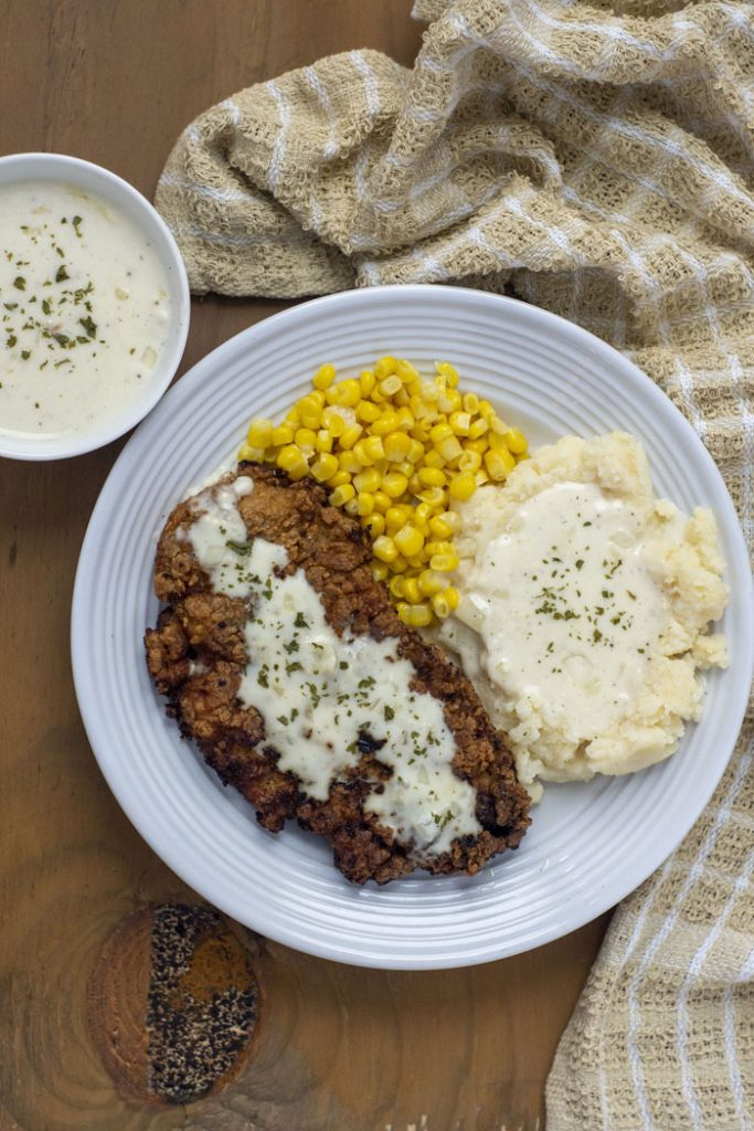 Overhead view of Creamy Buttermilk Chicken-Fried Chicken covered with white gravy next to mashed potatoes with gravy and steamed corn on a round white plate