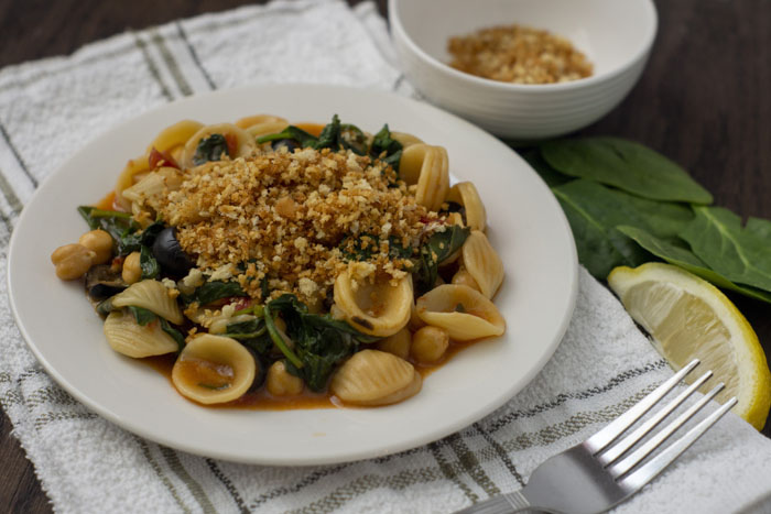 Chickpea and Spinach Orecchiette on a white plate on top of a white and green towel with a fork on it next to a small white bowl of toasted breadcrumbs and spinach and lemon slices